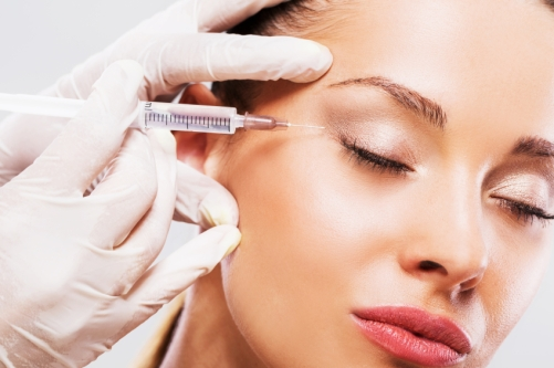 Woman with her eyes closed receiving Botox injection.